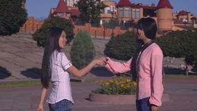 Portrait asian women greeting shake hands. Two female meeting outdoors say hello with friendly smile stock video footage