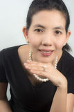 Portrait Asian Women Put the pearl jewelry in black Dress For pa Royalty Free Stock Image