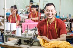 Asian worker in textile factory sewing using industrial sewing m. Portrait of asian worker in textile factory sewing using industrial sewing machine and smiling Royalty Free Stock Images