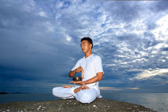 Portrait of Asian young man doing yoga on stone Royalty Free Stock Images