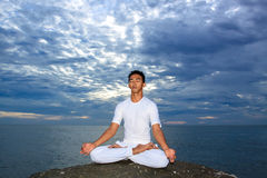 Portrait of Asian young man doing yoga on stone Stock Image