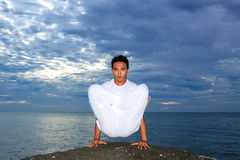 Portrait of Asian young man doing yoga on stone Royalty Free Stock Photography