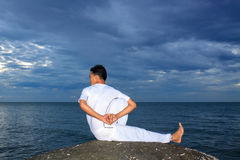 Portrait of Asian young man doing yoga on stone Stock Images