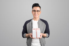Portrait of asian young man holding gift box isolated over gray. Background Stock Photo