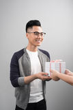 Portrait of asian young man holding gift box isolated over gray. Background Stock Image