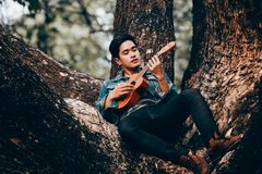 Asian young men play guitar Royalty Free Stock Photography
