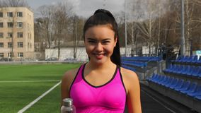 Asian young sporty girl with bottle of water in hands is walking on stadium after training. Portrait of asian young sporty girl with bottle of water in hands is stock video