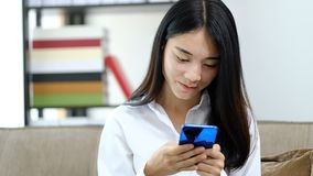Portrait Asian young woman playing reading text message on mobile phone at home stock video