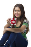Portrait of Asian young woman sitting of the floor and holding Coffee cup isolated Stock Photos