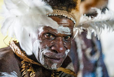 The Portrait Asmat warrior with a traditional painting and coloring on a face. Royalty Free Stock Photo