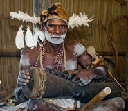 Portrait Asmat warrior with a tribal ritual drum. Stock Photography
