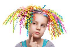Portrait assez astucieux de fille l'enfant avec le papier coloré se courbe dans sa pensée de cheveux image stock