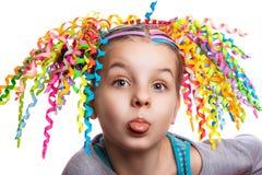 Portrait assez gai de fille l'enfant avec les boucles colorées de papier dans les cheveux montre la langue Émotions humaines photographie stock libre de droits