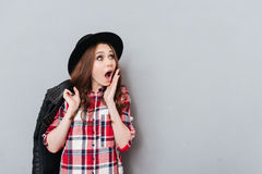 Portrait of an astonished amazed girl in plaid shirt. And hat looking away at copyspace isolated over gray background Stock Photography