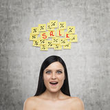 Portrait of an astonished girl. Yellow stickers with the word ' sale ' are hanged on the concrete wall. Stock Photography