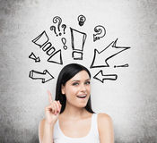A portrait of an astonished lady in a white tank top. Drawn arrows and questions marks around her head. Concrete backgrou Stock Photo