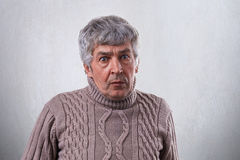 A portrait of astonished mature man with gray hair wearing sweater looking with wide open eyes into the camera while posing over w Royalty Free Stock Photography