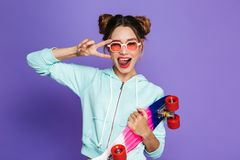 Portrait of astonished skater girl with two buns in sunglasses h. Olding skateboard and showing peace sign isolated over violet background in studio stock photos