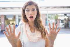 Portrait of astonished woman touching window with both hands Stock Image