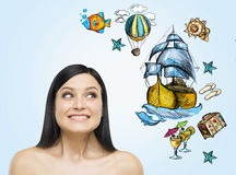A portrait of astonishing brunette woman who dreams about summer vacation. Nice summer sketches are drawn on the light blue backgr Stock Photos