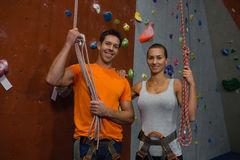 Portrait of athlete holding rope while standing by climbing wall at gym stock photography