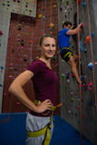 Portrait of athlete standing against trainer climbing wall at club Royalty Free Stock Photos