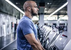 Portrait of an Athlete on a treadmill listening to music. He is exhausted and thinks about something, he had a hard workout royalty free stock images