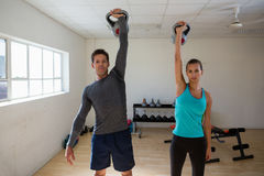Portrait of athletes lifting kettlebells in gym. Portrait of confident athletes lifting kettlebells in gym Stock Photos