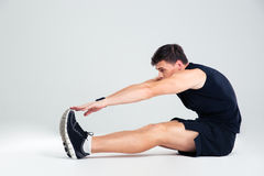 Portrait of athletic man doing stretching exercises Royalty Free Stock Images