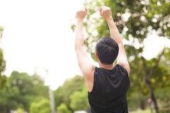 portrait of athletic man winning and raising his hands up in the air. Stock Photography