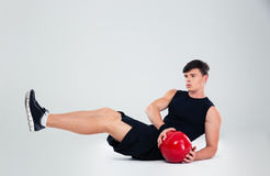 Portrait of athletic man workout with fitness ball. Isolated on a white background Royalty Free Stock Photo