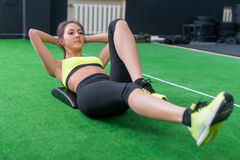 Portrait of an athletic woman doing exercising abdominals work-out lying in gym Stock Photo
