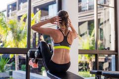 Portrait of an athletic woman doing exercising abdominals work-out lying in gym at luxury hotel at summer.  stock images