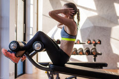 Portrait of an athletic woman doing exercising abdominals work-out lying in gym at luxury hotel at summer.  Stock Photos