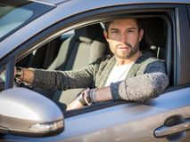 Handsome man sitting in his car. Portrait of attractiave man in business suit sitting in his new stylish car outdoor in city Stock Photos