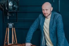 Portrait of attractive adult successful bald bearded man in suit on blue background, blogging, TV host royalty free stock image