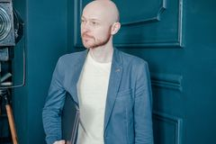 Portrait of attractive adult successful bald bearded man in suit with laptop near blue wall royalty free stock photos