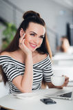 Portrait of an attractive adult woman with perfect smile holding a cup of coffee and looking away happily. Stock Photos