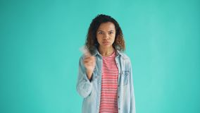 Portrait of attractive African American lady waving finger and shaking head. Meaning no standing on bright blue background. Youth, human reactions and people stock footage