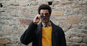 Portrait of attractive African American student taking off sunglasses outside. Portrait of attractive African American man student taking off sunglasses outside stock video footage