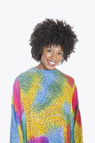 Portrait of an attractive African American woman in multicolored dashiki standing over gray background Stock Image