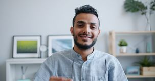 Portrait of Arabian man taking off glasses looking at camera smiling at home stock footage
