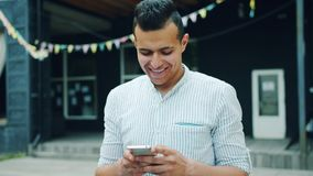 Portrait of attractive Arabian man using smartphone touching screen outdoors. Standing in city street alone. Devices, people and modern youth concept stock footage