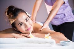 Thai oil massage to beautiful Asian woman. Portrait of attractive Asian beautiful woman in spa club. Body care treatment by Thai oil. Cute girl having massage at royalty free stock images