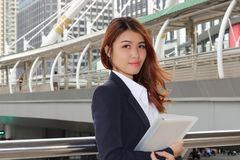 Portrait of attractive Asian business woman holding binder in her hands at urban building outdoor background. Portrait of attractive Asian business woman Royalty Free Stock Image