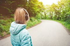 Portrait of an attractive athletic blonde girl from back to light running down jacket, wearing bluetooth headphones with royalty free stock images