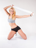 Portrait of attractive athletic caucasian woman with long blond hair isolated on gray studio shot with towel stretching royalty free stock photo