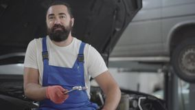 Portrait attractive bearded mechanic posing with spanner sitting on the hood of a broken car in a car repair shop. stock video footage