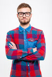 Portrait of attractive bearded young man  with arms crossed. Portrait of attractive bearded young man in checkered shirt and glasses with arms crossed Royalty Free Stock Photography