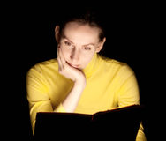 Young woman reading glowing book Stock Photography